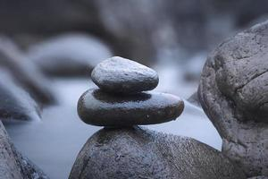 A closeup shot of rocks on a blurred river background photo