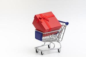 shopping cart present box with color ribbon on white background photo