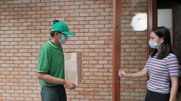 leveransman med ansiktsmask ger paket till en asiatisk kvinna video
