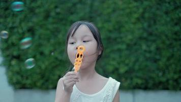 Asian girl playing by blowing soap bubbles video