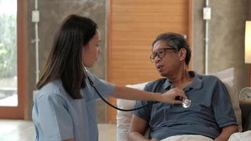 Female doctor checking health of elderly Asian male patient at home video