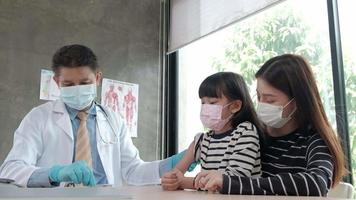 Male doctor vaccinating Asian girl At the pediatrics clinic video