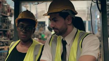 Black female engineer and caucasian male forklift driver video