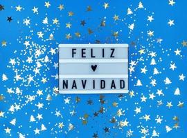 Light box with Feliz Navidad phrase, Spanish Merry Christmas on blue photo