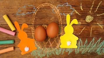Two Easter bunnies made of paper and eggs in a basket. photo