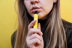 A young girl smokes disposable electronic cigarette photo