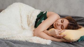 Hermosa joven en un camisón verde duerme sobre una almohada amarilla foto