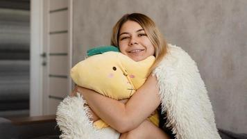Happy blonde in the morning hugs a yellow pillow. Morning concept photo