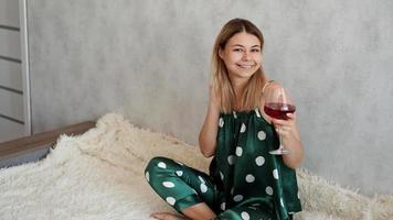 chica en pijama verde en la cama con una copa de vino tinto foto