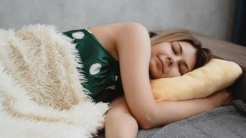 Beautiful young girl in a green nightie sleeps on a yellow pillow photo