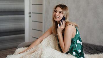 Atractiva mujer joven sentada en la cama y hablando por teléfono inteligente foto