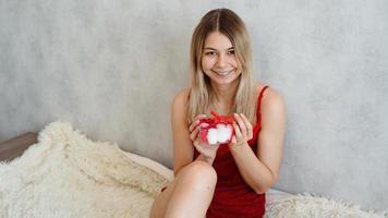 Retrato de niña linda recibir caja de regalo, disfrutando del presente en casa foto