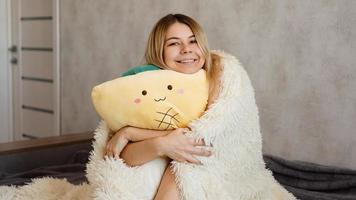 rubia feliz por la mañana abraza una almohada amarilla. concepto de mañana foto