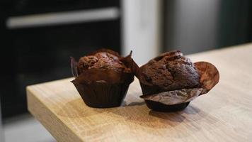 Dos muffins de chocolate sobre una mesa de madera contra la cocina moderna foto