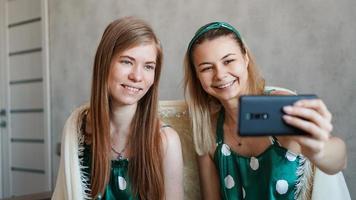 Hermosas novias felices tomando selfie con smartphone foto