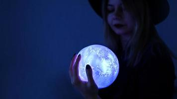 A young woman fortune teller in a hat is holding a magic ball. photo