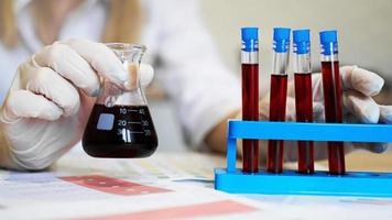 Mano de un científico tomando un tubo de muestra de sangre del soporte foto