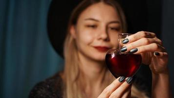 Cropped image of woman holding heart shaped glass jar of love potion photo
