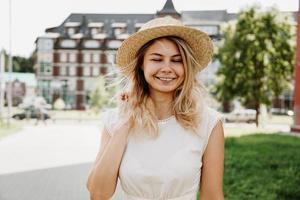 una hermosa rubia camina por una ciudad. mujer vestida de blanco foto
