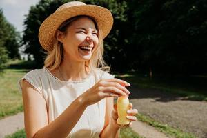 Close portrait of blonde woman in straw hat. She laughs photo