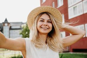 Sonriente joven chica rubia alegre con sombrero haciendo selfie foto
