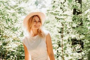 Hermosa joven con sombrero de paja y vestido blanco en un parque verde foto