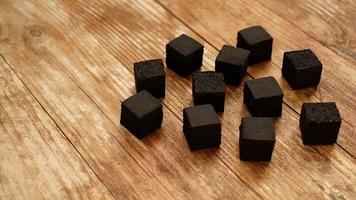 Cubes of coconut coal for hookah on wooden background. photo