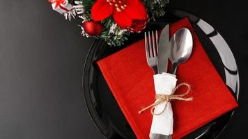 Setting for festive Christmas dinner on black table with decoration photo