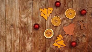 Dry oranges, red balls and wooden christmas figurines photo