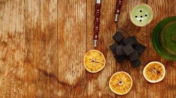 Coals for hookah on wooden background with dry oranges photo