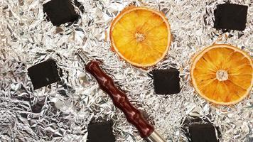 Coals for hookah on foil background with dry oranges photo