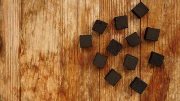 Cubes of coconut coal for hookah on wooden background. Top view photo