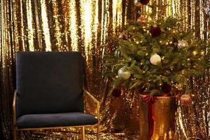 New Year interior. Christmas tree with gold decorations. photo