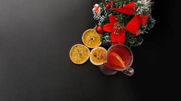 Mulled wine in glass on black table with New year decoration photo