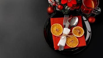 Ajuste para la cena navideña en mesa negra con decoración foto
