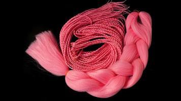 kanekalon rosa cuelga sobre un fondo negro foto