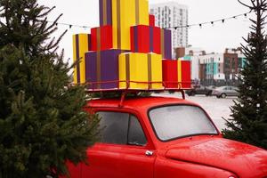 Christmas red retro car with gift boxes outside photo