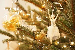 hermosa bailarina decora una rama de árbol de navidad foto