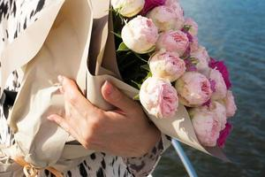 A young girl with a bouquet of bright flowers on a cruise ship photo