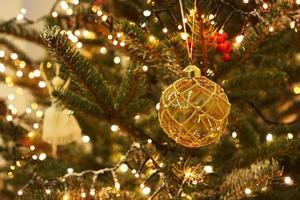 Decoración navideña en forma de bola en árbol real. foto