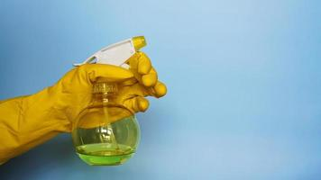 Mano en guante de goma amarillo sosteniendo spray de plástico foto