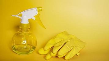 guantes de goma y una botella de spray de plástico foto
