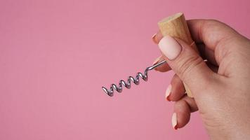 Female hand holding vintage corkscrew bottle opener photo