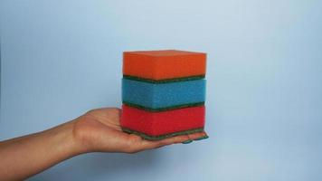 Hand holds different sponges on blue background. photo