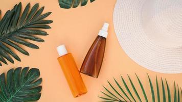 crema solar, sombrero para el sol, botella de loción sobre fondo naranja suave foto