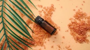 Botella cosmética con aceite sobre un fondo de sal marina foto