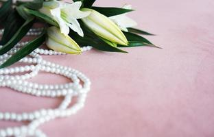 White lilies and a necklace of pearls on a pink background. photo