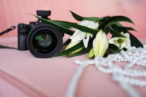Black camera with a lens and white lilies and a necklace of pearls photo