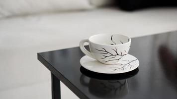 White coffee cup with a pattern of black branches on a black table photo