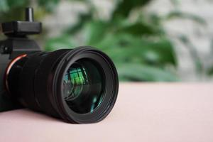 Black camera with a lens on a blurred background of green leaves. photo